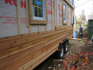 The far wall with half of the siding up.
