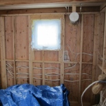 The bunch of wires on the lower right of the photo are all ready to go to the panel which will go into the wall dividing the bathroom from the kitchen - the only interior wall in the house. The grey tube in the top right of the photo is the housing for the HRV unit. The tube will be cut down to size later on.