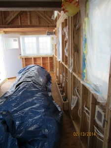 A view of the whole wall ready for spray foam.  You can also see the box built around the wheel well.  The big blue tarp is covering/protecting the interior siding that have to be stored inside the tiny house.