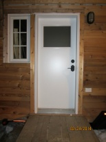 """My door. The company I ordered my door from sent me a door that was ½"""" too short back in October. The new door arrived this week and was installed on Thursday. The window is a little crooked, but that's an easy fix - it's the same window as the door that was too short and I watched him put the window in, so with a little help, I can get the window squared away. Also note that there is a door handle and a lock! I have keys and everything."""